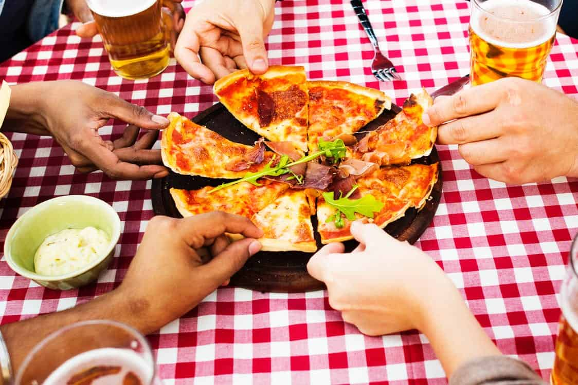 people holding a slice of pizza with beer