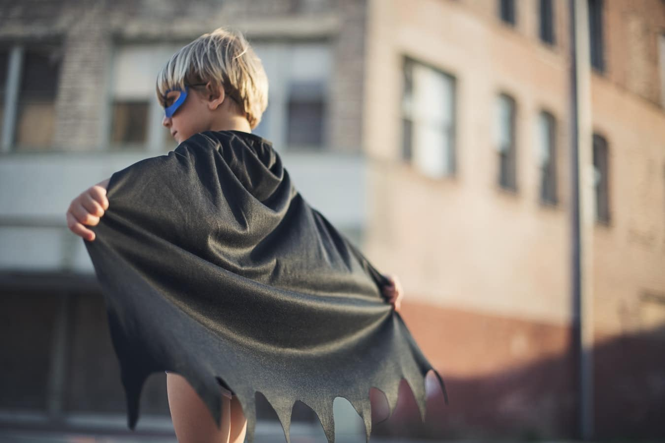boy in a superhero costume with cape and mask