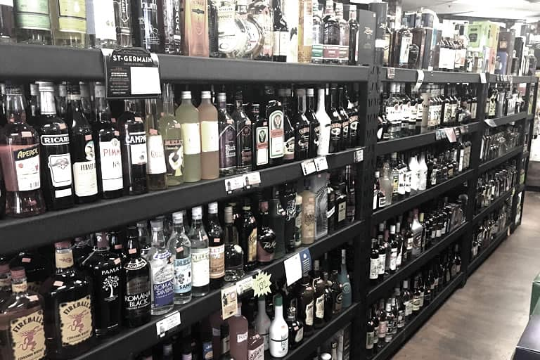 Liquor bottles on a store shelf. Many 50th birthday party themes feature an open bar for guests.