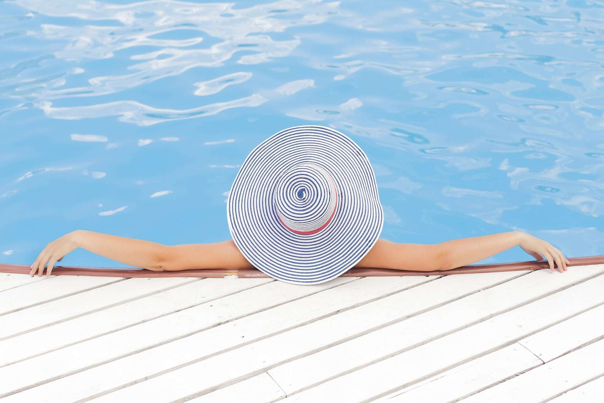 lady with hat lounging in pool