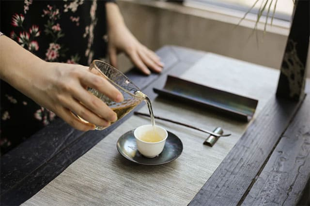 Woman pouring tea on white cup