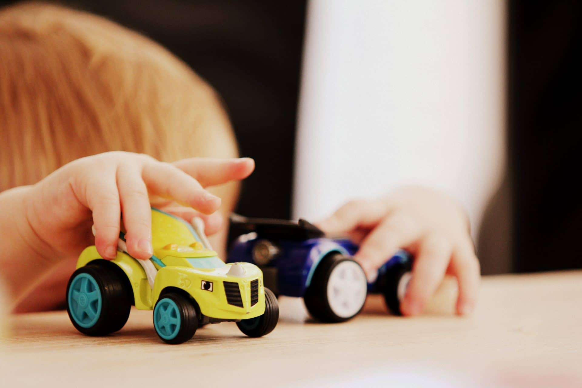 child playing with two car toys