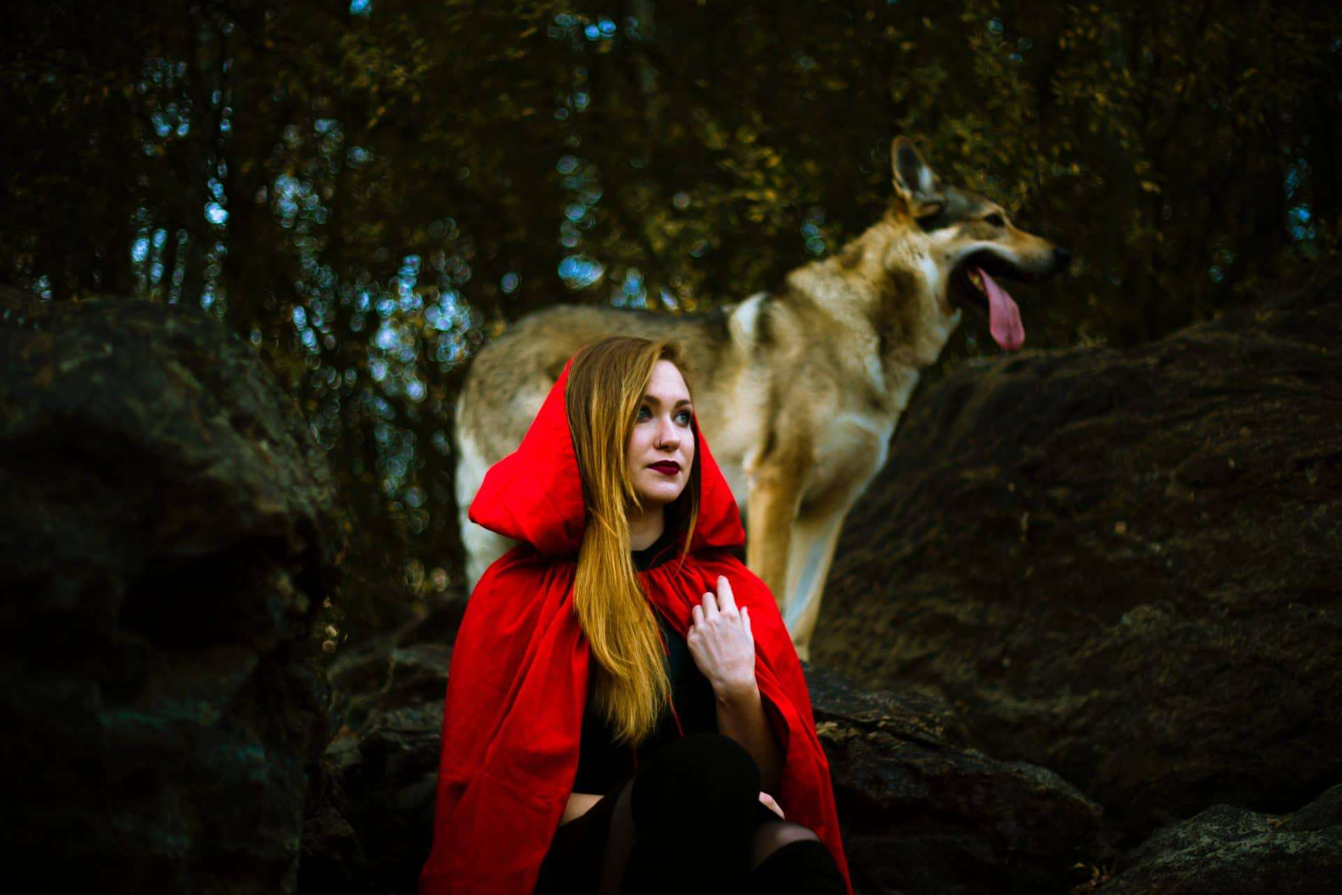 Women wearing a red hoodie cape and at her back is a dog