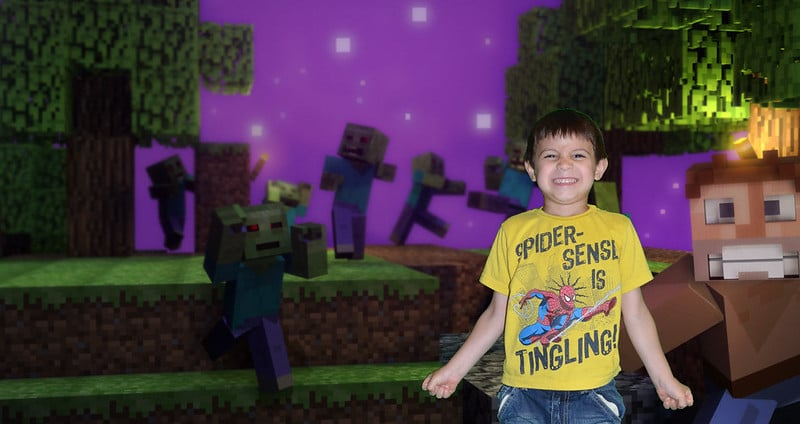 boy standing in front of a Minecraft image